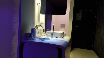Yhden hengen huone tilavalla tuplasängyllä. Lavuaari ja vessa ovat samaa avotilaa.